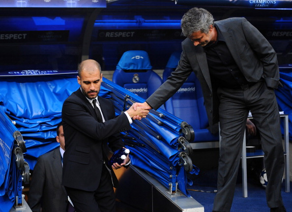 Barcelona's coach Josep Guardiola (L) and Real Madrid's Portuguese coach Jose Mourinho shake hands before the Champions League semi-final first leg football match between Real Madrid and Barcelona at the Santiago Bernabeu stadium in Madrid on April 27, 2011. AFP PHOTO/LLUIS GENE (Photo credit should read LLUIS GENE/AFP/Getty Images)
