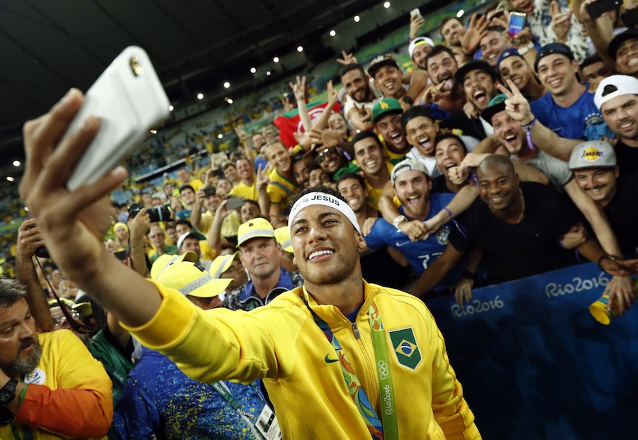 TOPSHOT - Brazil's forward Neymar poses for a selfie with fans as they celebrate after the Rio 2016 Olympic Games men's football gold medal match between Brazil and Germany at the Maracana stadium in Rio de Janeiro on August 20, 2016. / AFP / Odd ANDERSEN (Photo credit should read ODD ANDERSEN/AFP/Getty Images)